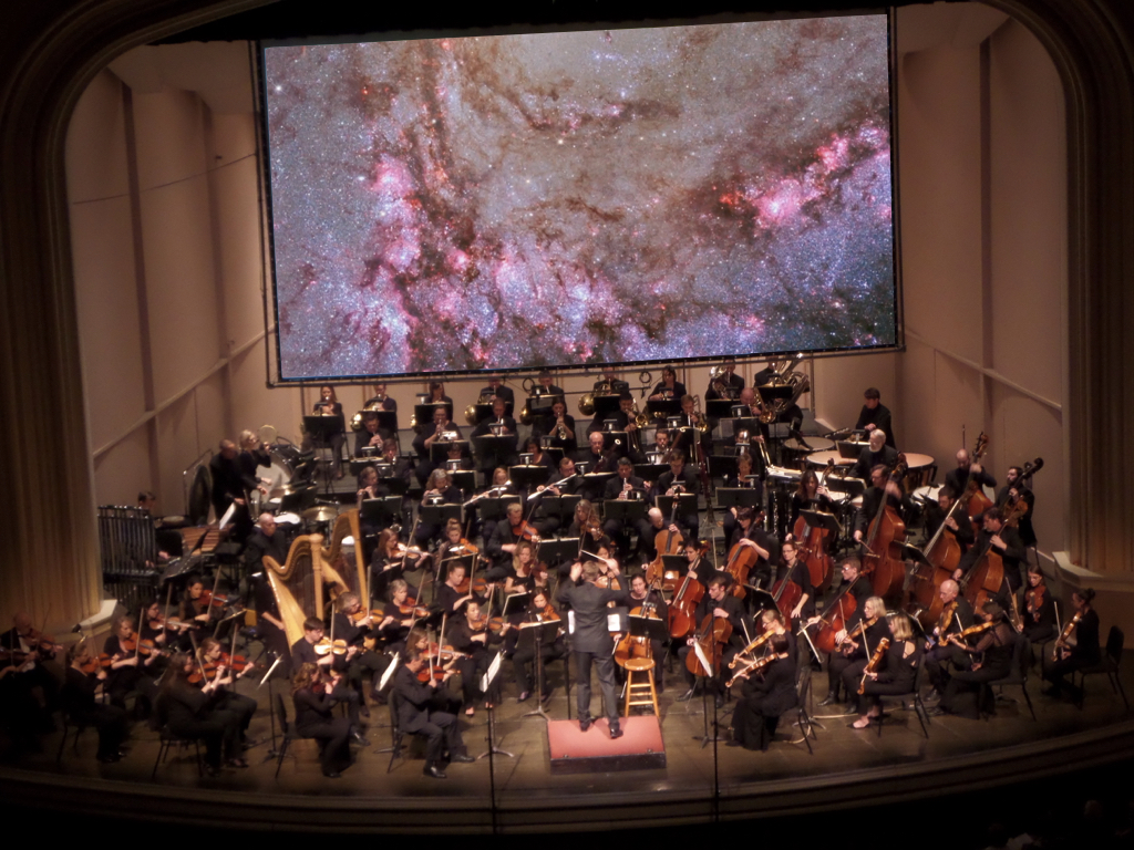 Boulder Phil plays music about stars and astronomers and planets in front of screen displaying beautiful space images