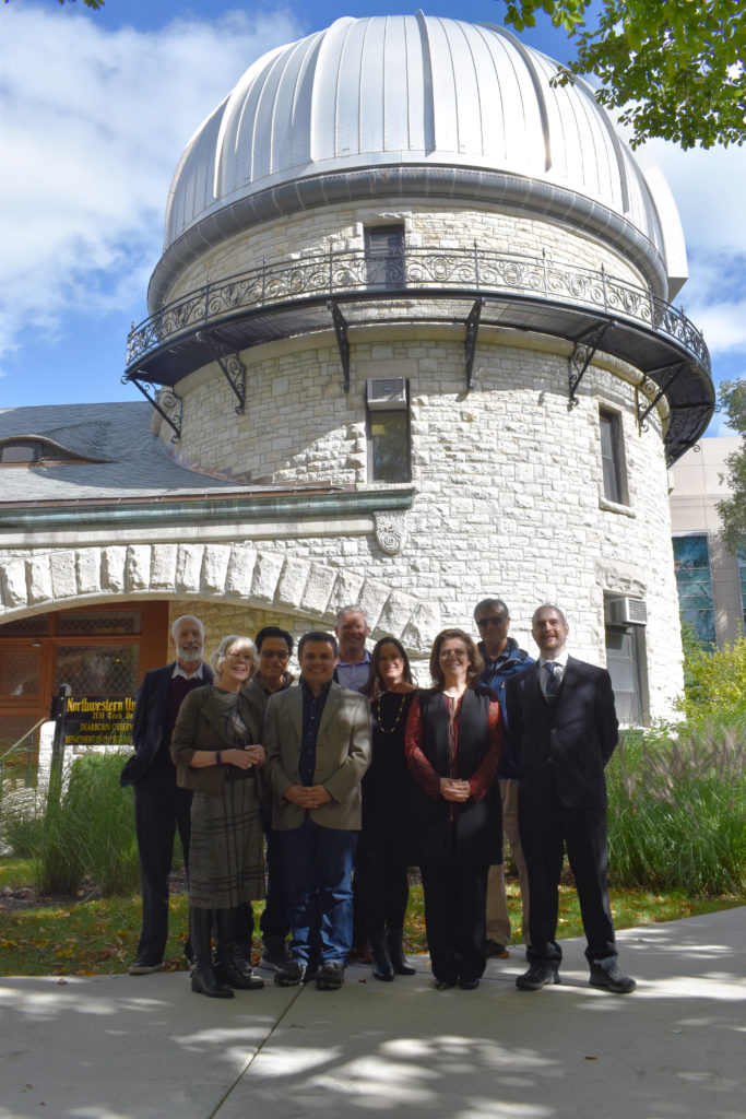 Board of Visitors members standing in front of Dearborn Observatory building on a sunny day